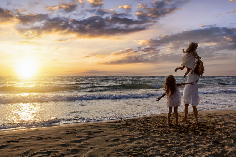 Mother and her daughters enjoy the sunset on the beach Sunset Sky Sea Water Beach Horizon Over Water Women Horizon Leisure Activity Cloud - Sky Togetherness Love Positive Emotion Lifestyles Scenics - Nature Family Mother Daughter Summer Vacations Happiness Enjoying Life Holding Children Beauty In Nature