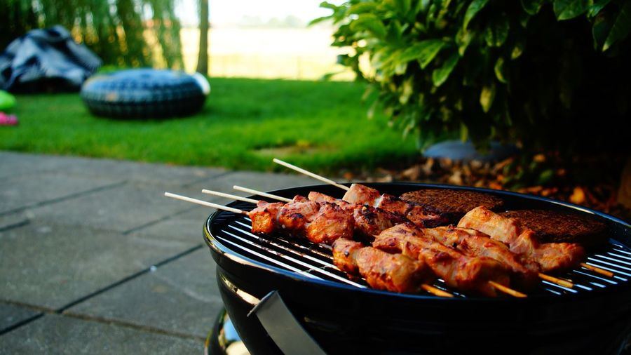 Close-up of meat on barbecue grill in yard