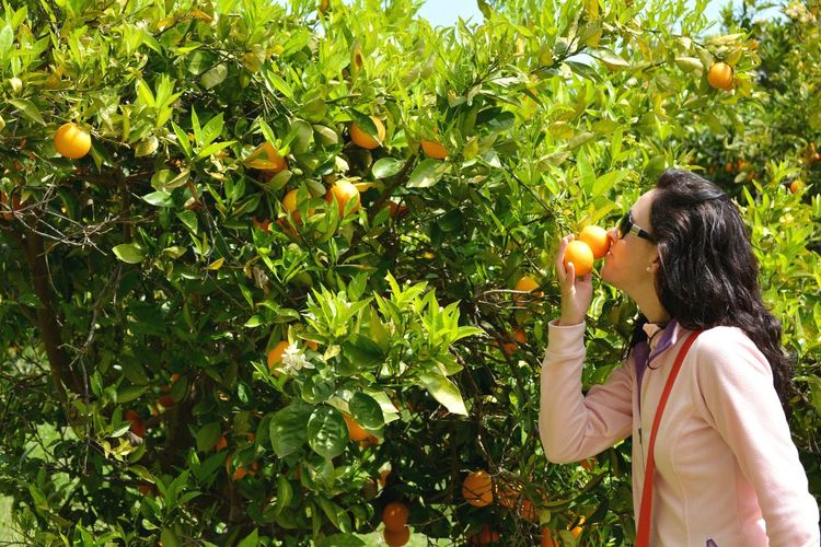 Woman smelling oranges while standing against plants