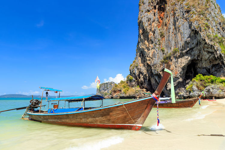 Boat moored on beach against blue sky