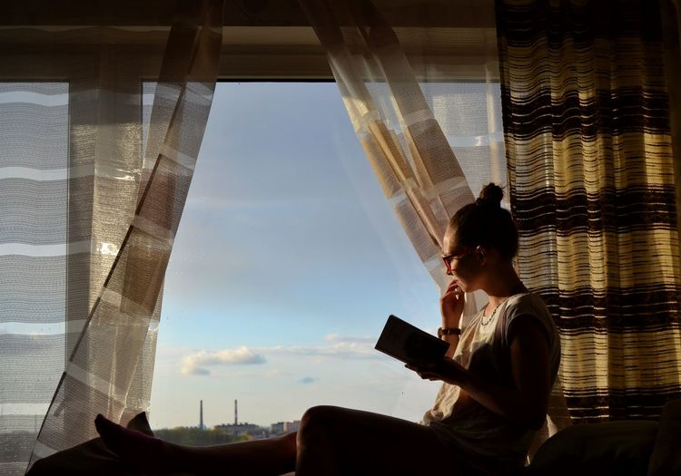 Side view of woman with book sitting on window at home
