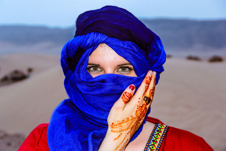 Close-up portrait of young woman covering face with blue headscarf at desert