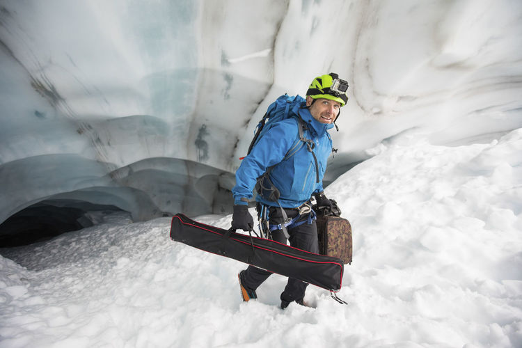 Man with umbrella on snow during winter