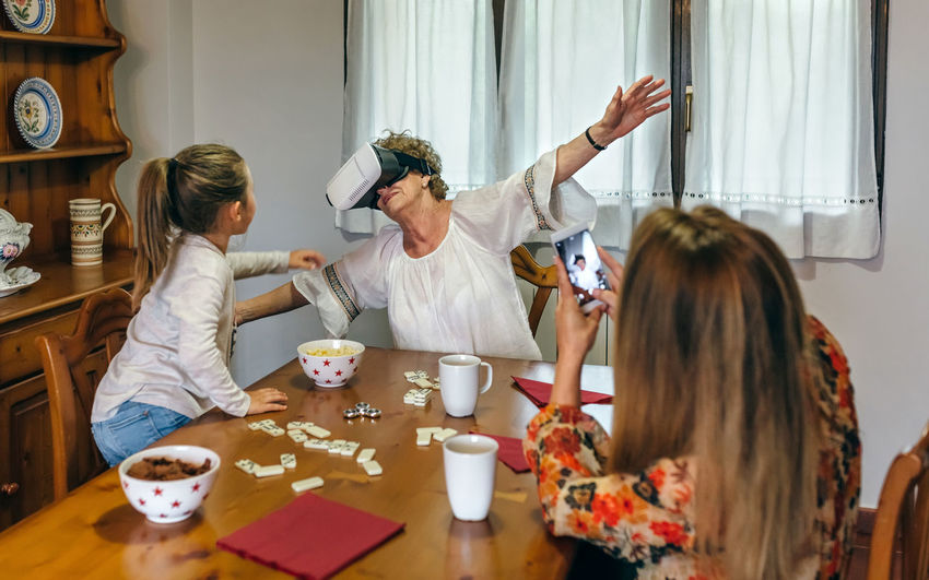 Grandmother with daughter and granddaughter wearing virtual reality simulator at home