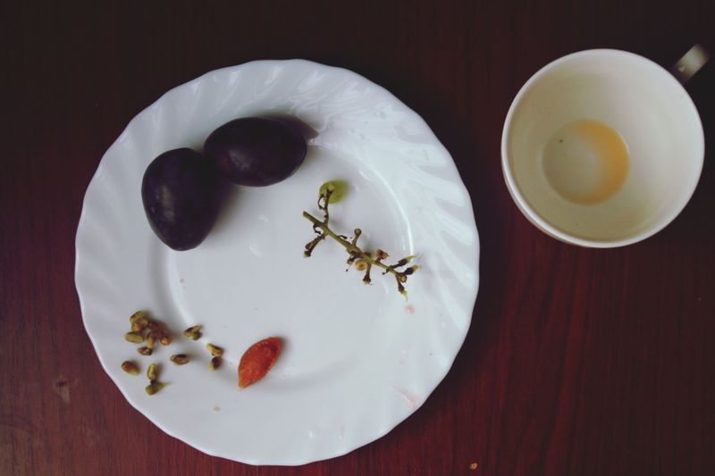 Directly above shot black grapes and leftovers in plate on table
