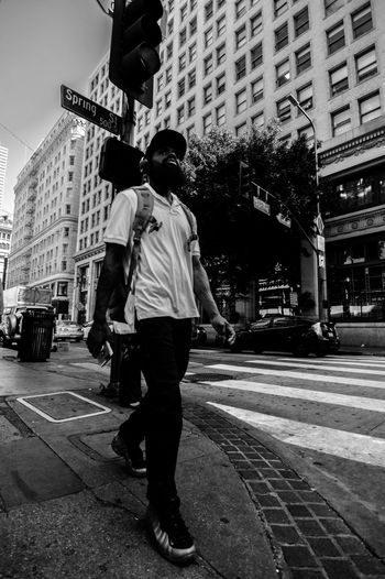 Rear view of man walking on street amidst buildings in city