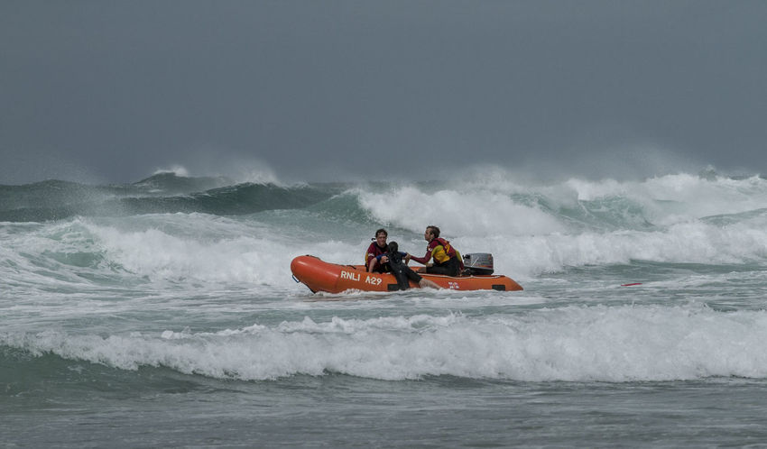 Lifeguards pull a boy from the surf after he had got into difficulty in the surf Inshore Lifeboat Rescue RNLI Safety Sea Water Waves
