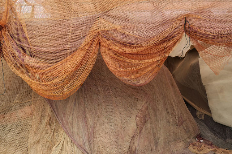 draped orange colored fishing nets Fishing Net Hanging Backgrounds Brown Close-up Draped Fabric Fabric Full Frame Linen Netting No People Pattern Textile Texture Veiled