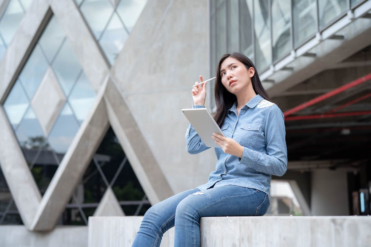 Young woman looking away while sitting on mobile phone