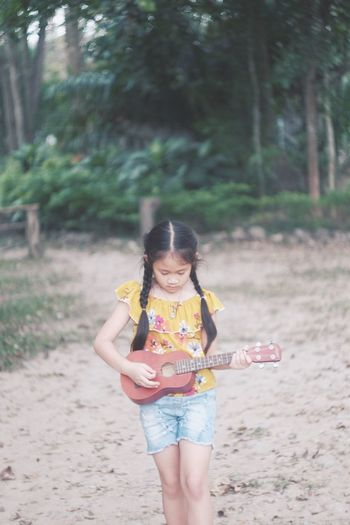 Girl playing ukulele while standing against trees