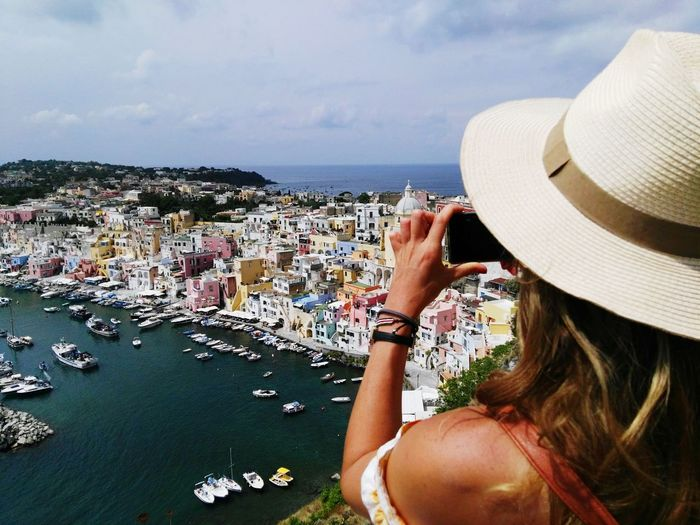 Woman photographing sea and cityscape