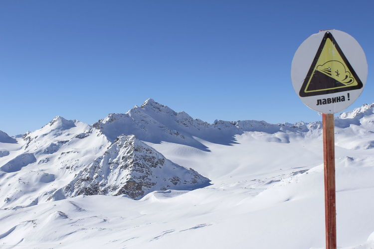 Warning sign by snow covered mountains against clear blue sky