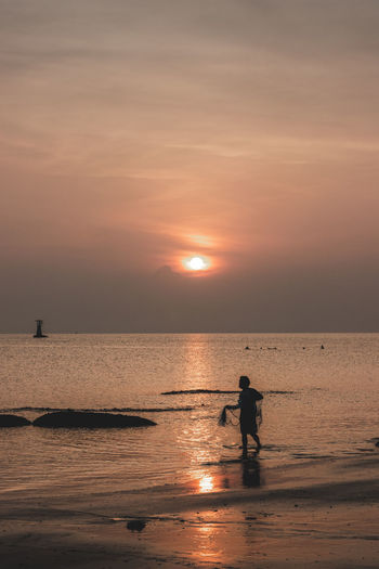 Man standing at sea against sky during sunset