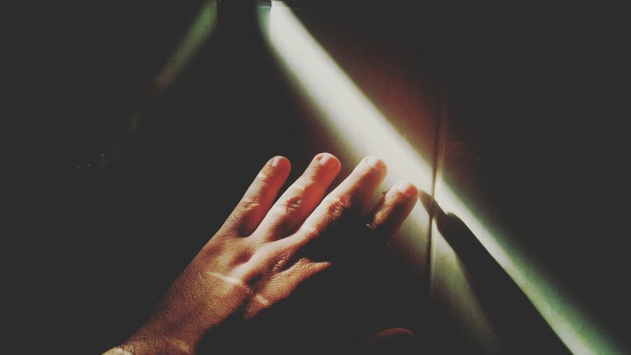 Close-up of human hand in darkroom
