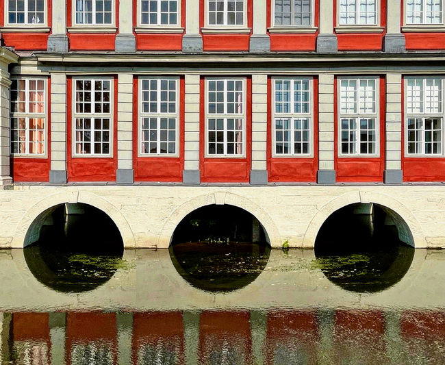 Arch bridge over canal by buildings in city