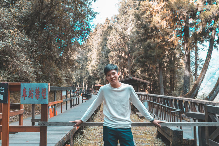 One Person Tree Real People Plant Casual Clothing Young Adult Leisure Activity Lifestyles Looking At Camera Portrait Front View Three Quarter Length Standing Young Men Railing Day Nature Smiling Outdoors