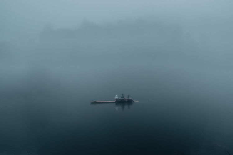 High angle view of boat sailing on lake during foggy weather