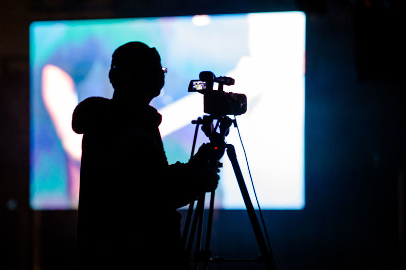 Silhouette man with camera standing in front of screen in studio