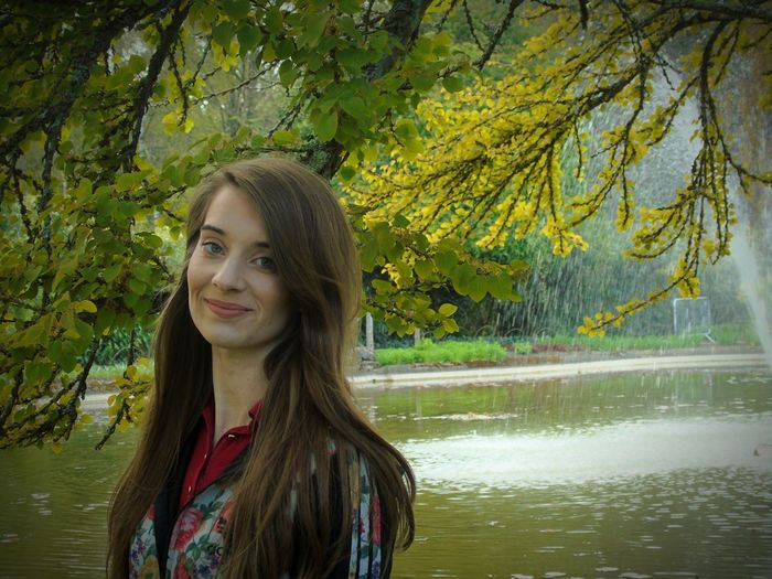 Portrait of smiling young woman standing by pond in garden