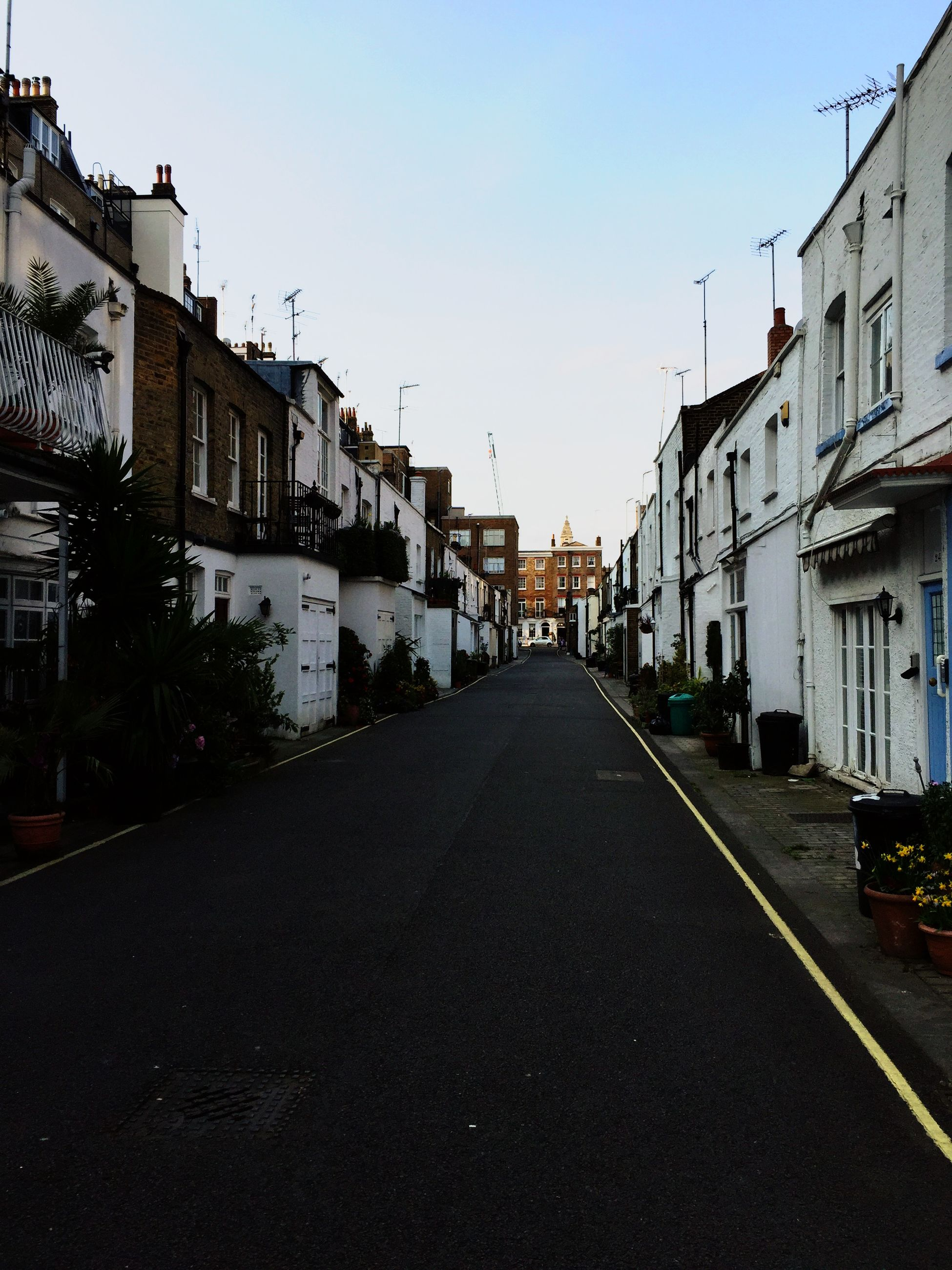 building exterior, architecture, built structure, clear sky, the way forward, diminishing perspective, street, residential structure, house, residential building, road, city, copy space, vanishing point, blue, building, long, transportation, empty, residential district