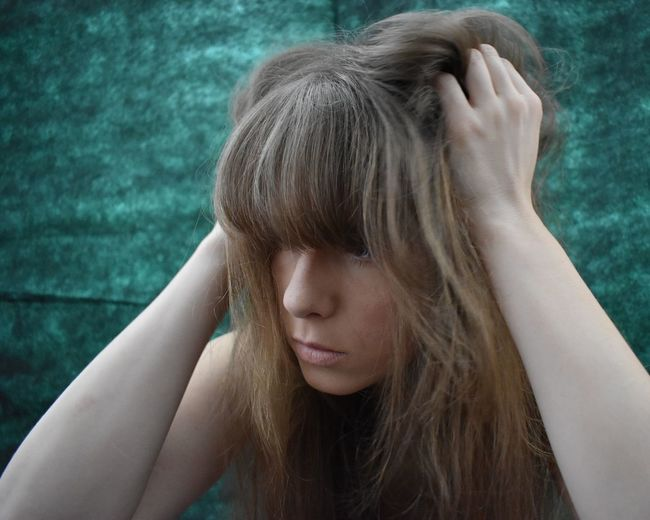 Close-Up Of Young Woman With Hand In Hair