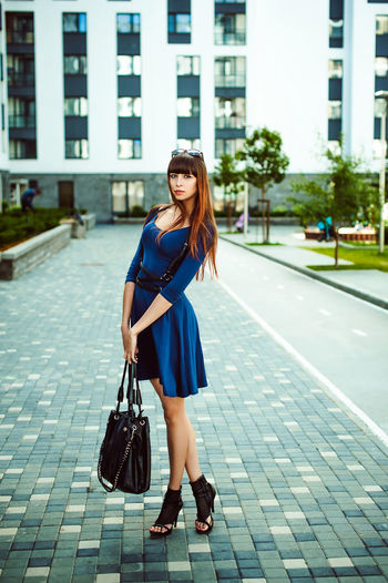 Full length portrait of young woman standing in city