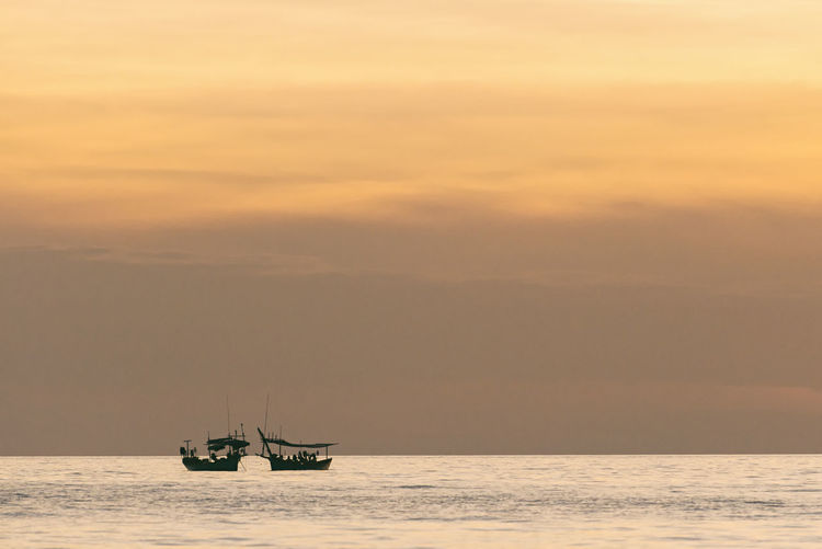 Fishing Boats Sea Sunset Beauty In Nature Tranquil Scene Nature Idyllic Fishing Boat Tranquility Silhouette Calmness Tranquility ASIA Cambodia Fishing Boats Vacations Copy Space Backgrounds Summer Peace Beauty In Nature Beautiful Travel Relaxing Sky Scenics