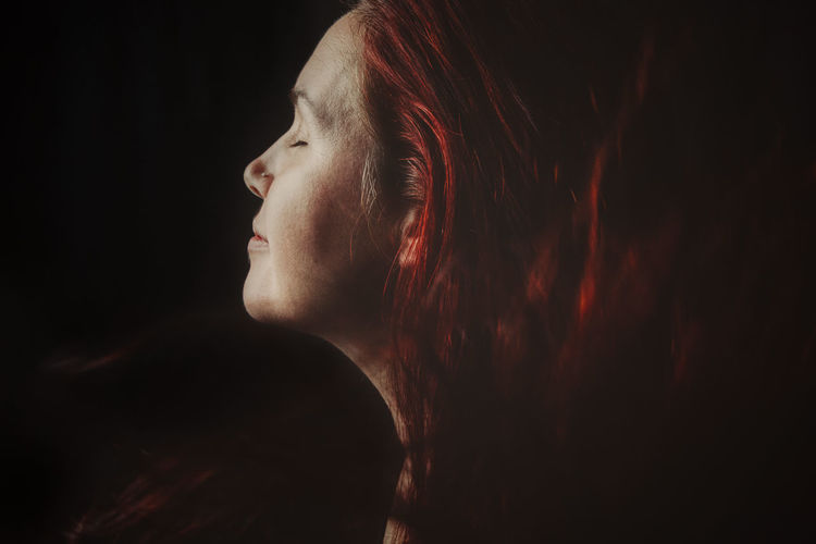 Close-up of woman looking away against black background
