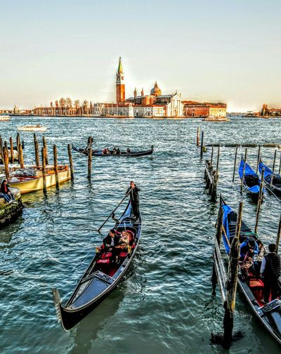 Gondolas in grand canal by san marco campanile against clear sky