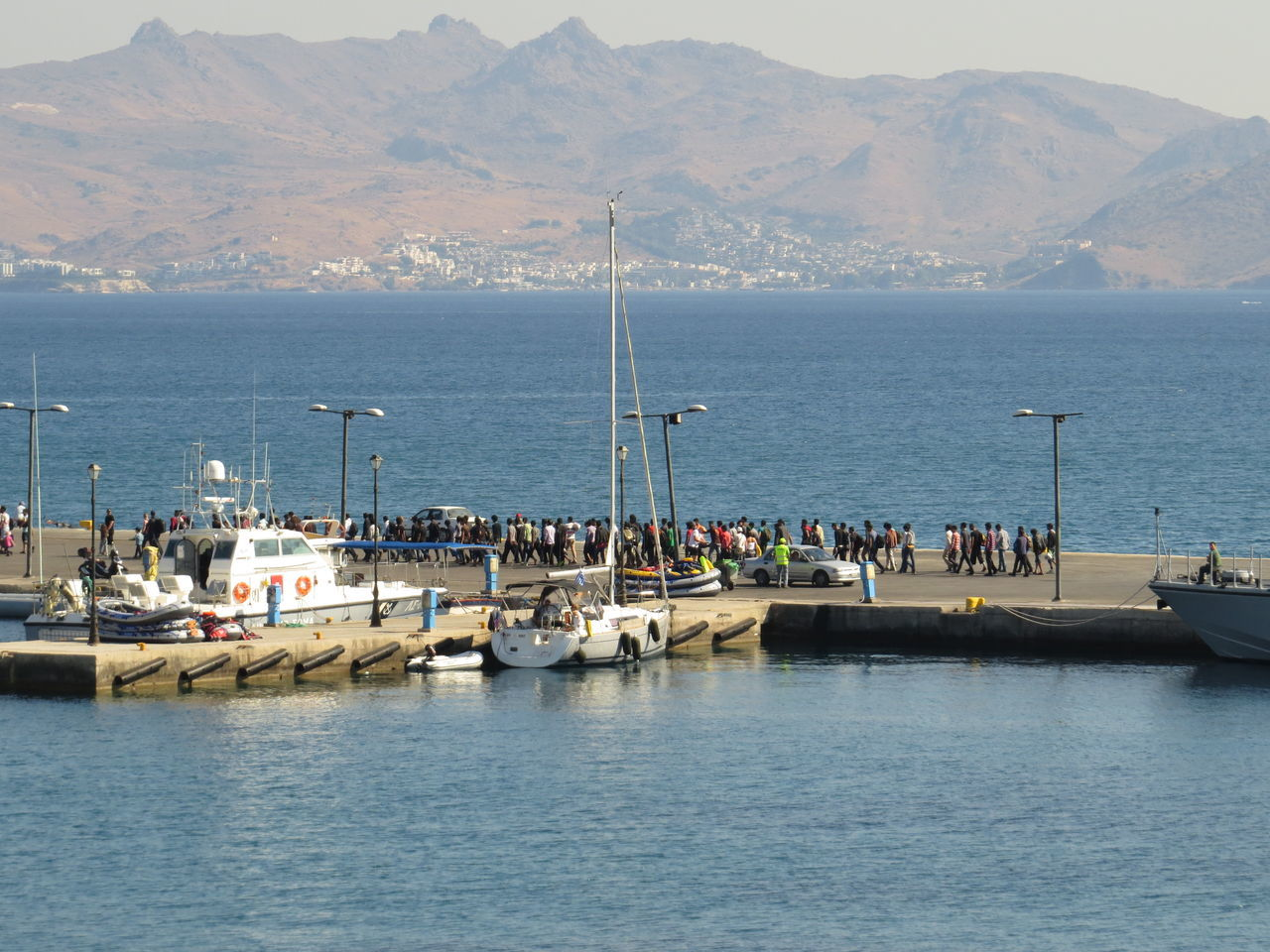 People On Pier At Port On Sea Against Mountains