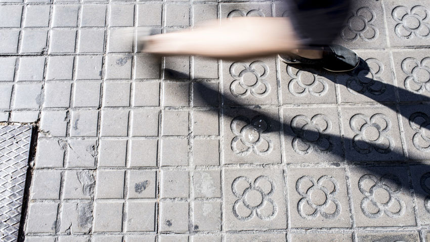 Body Part Day Footpath High Angle View Human Body Part Human Leg Human Limb Leisure Activity Lifestyles Low Section Motion One Person Outdoors Pattern Paving Stone Real People Shoe Street Tiled Floor Unrecognizable Person Walking