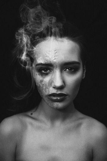 Close-up portrait of topless woman with burnt face against black background