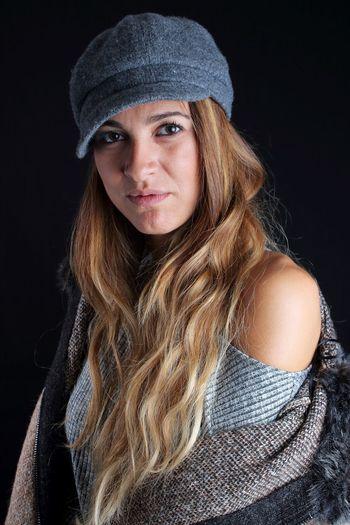 Portrait of woman wearing cap against black background