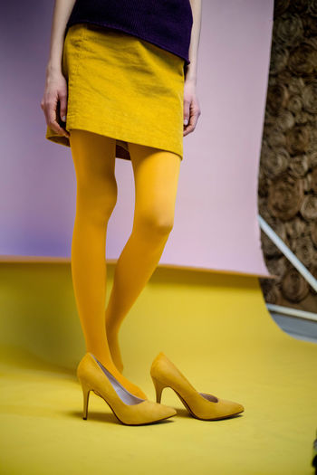 Low section of woman standing in yellow shoes