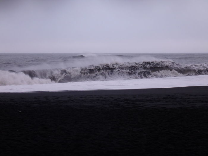 Waves splashing in sea against clear sky during high tide