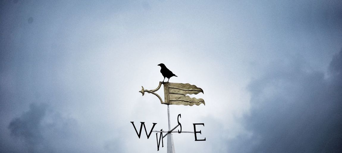 Low angle view of weather vane against clouds