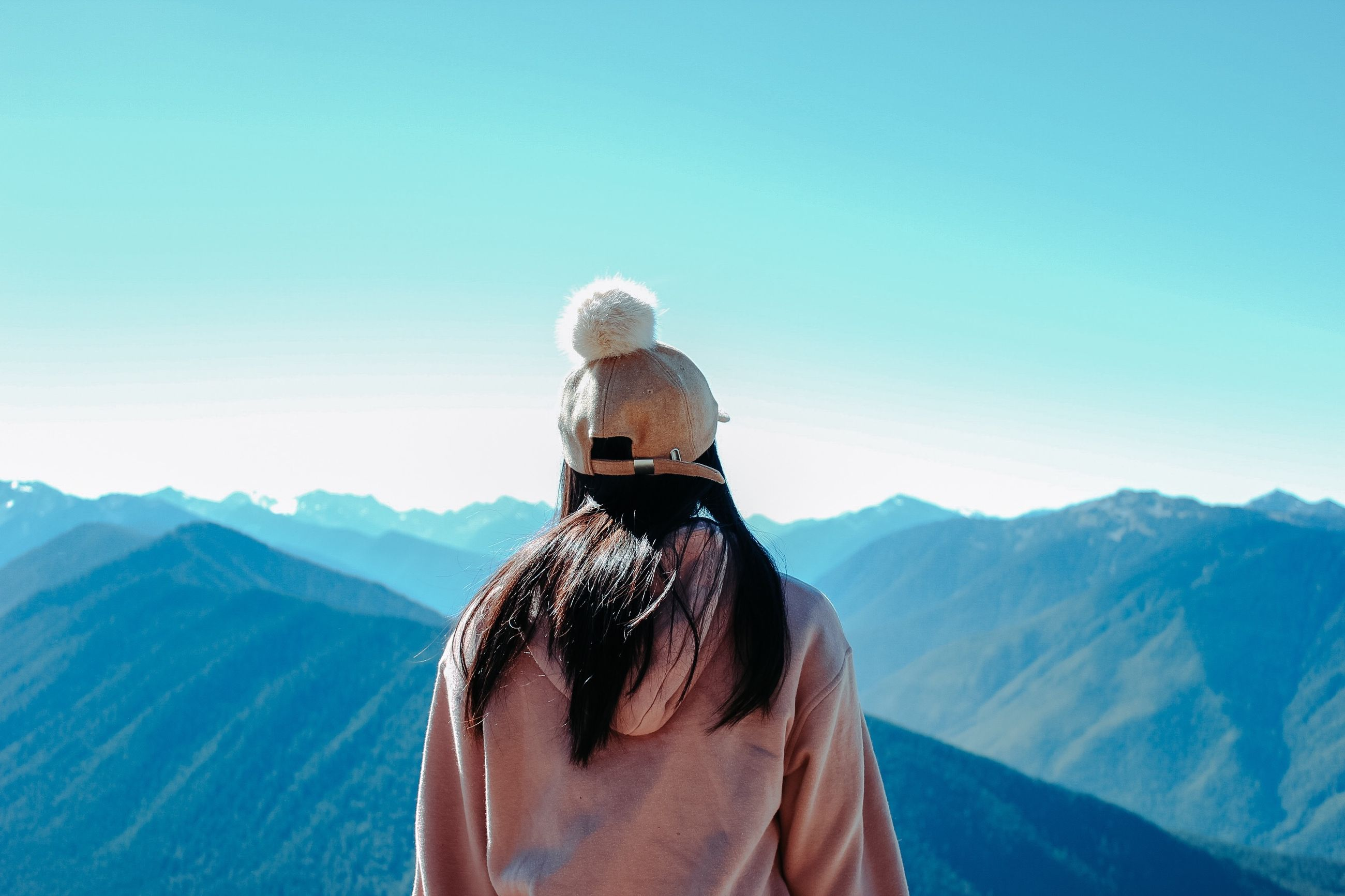 rear view, mountain, sky, real people, beauty in nature, leisure activity, one person, lifestyles, winter, scenics - nature, nature, mountain range, tranquil scene, adult, day, women, clear sky, copy space, holiday, warm clothing, looking at view, hairstyle