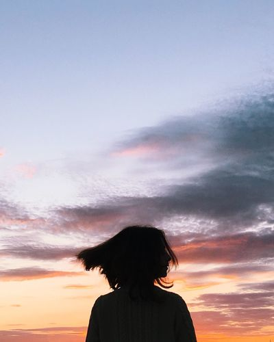 Woman with tousled hair standing against sky during sunset