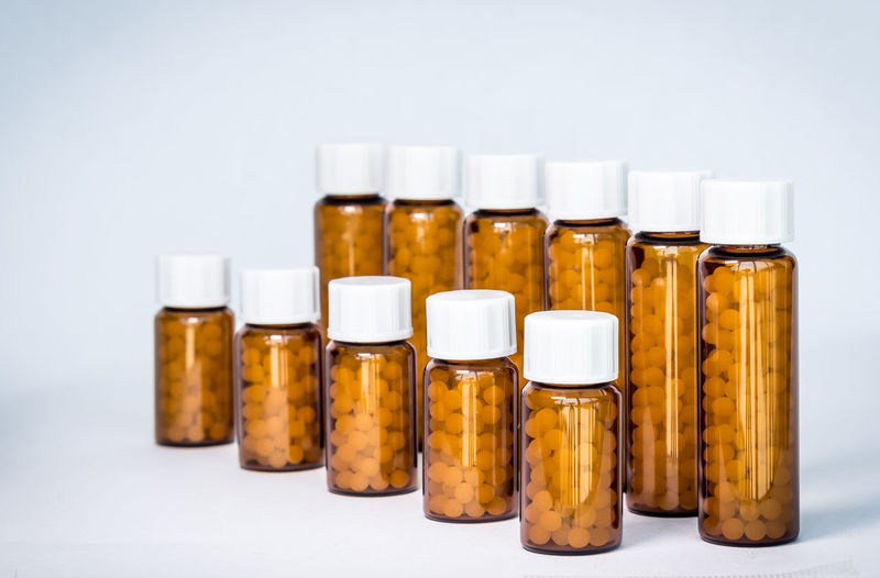 Close-up of medicines in bottle against white background