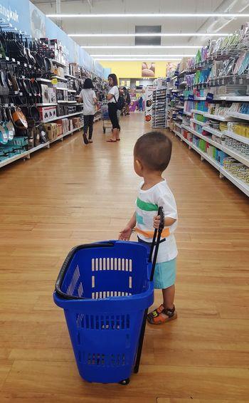 Full length of boy with blue bucket standing on hardwood floor in supermarket