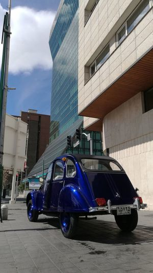 City Built Structure Building Exterior Car Architecture No People Outdoors Sky Vehicle Mirror Day Beauty EyeEmNewHere Adapted To The City Luxury Modern Transportation Mode Of Transport Streetphotography Blue Old Car City Street Photography Street Low Angle View Architecture