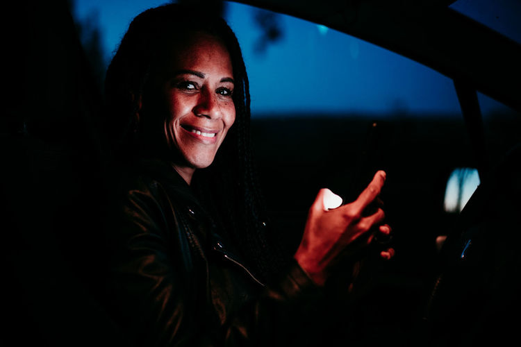 Portrait of smiling woman using mobile phone while sitting in car