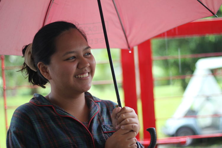 Smiling Woman Holding Umbrella During Rainy Season