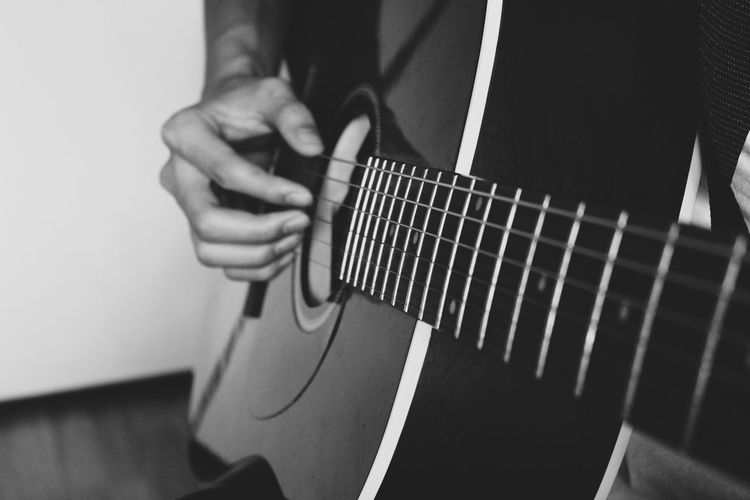 Close-up of man playing guitar