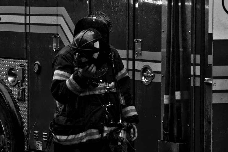 Front View Of Firefighter Standing Against Engine At Station