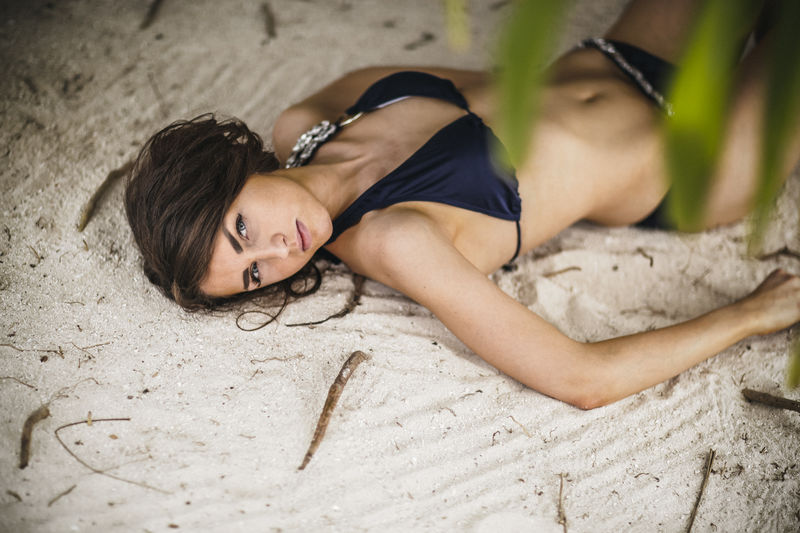 High Angle View Of Young Woman Lying On Beach