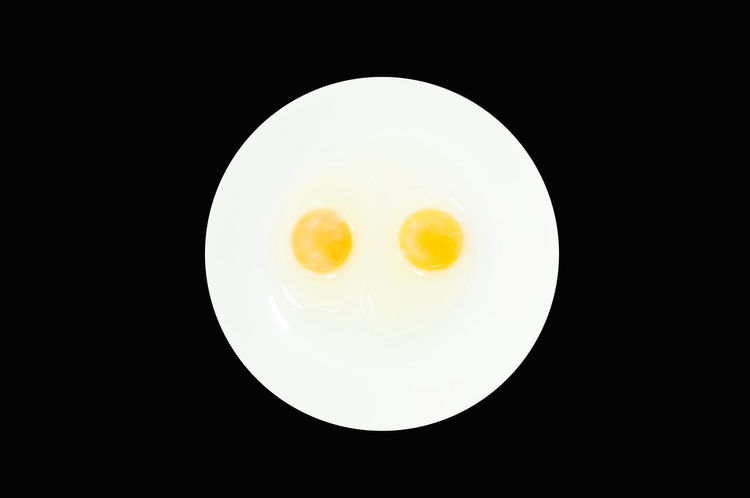 Raw egg yolks in a white bowl isolated on a black background, To prepare for a high protein diet has helped in the growth of a person's body Breakfast Cuisine Fresh Ingredient Isolated Protein Uncooked White Yellow Yolk Chicken Cooking Art Black Background Bowl Chicken Egg Egg Egg Yolk Eggcup Food Food And Drink Healthy Healthy Eating Organic Food Raw Food