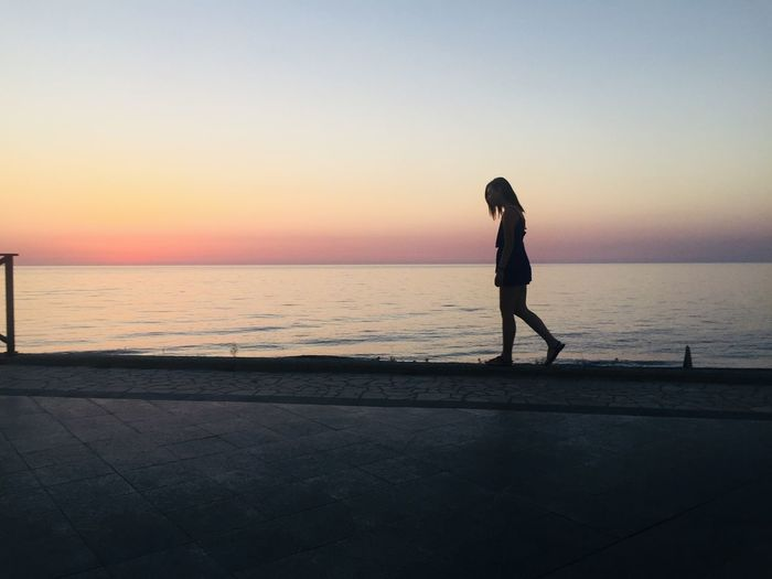 Side view of silhouette woman walking on retaining wall against sea during sunset