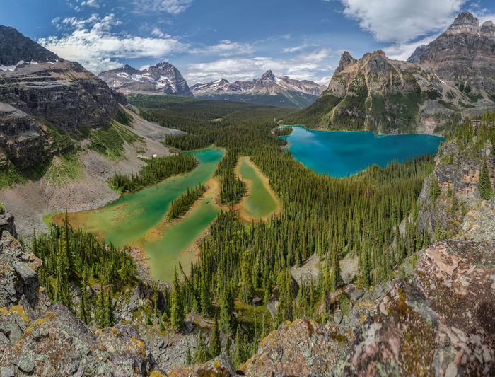 A 20 shot panorama looking down over Lake OHara and Mary Lake. I would normally not shoot photos in the middle of the day however you really can't appreciate the spectacular colours of these lakes unless you have overhead sun. Ten minutes before I took these shots the family sheltered in a small rock cave while a hail storm passed over. We experienced the full gamut of Canadian alpine summer weather on this trip with rain, hail, snow, wind and sunshine at various times. Yoho National Park, British Columbia, Canada Love Life, Love Photography Blue Color British Columbia, Canada Mary Lake Panoramic Beauty In Nature Cloud - Sky Day Environment Green Color Idyllic Lake Lake Ohara Landscape Mountain Mountain Range Nature No People Non-urban Scene Outdoors Scenics - Nature Sky Tranquil Scene Tranquility Water Yoho National Park