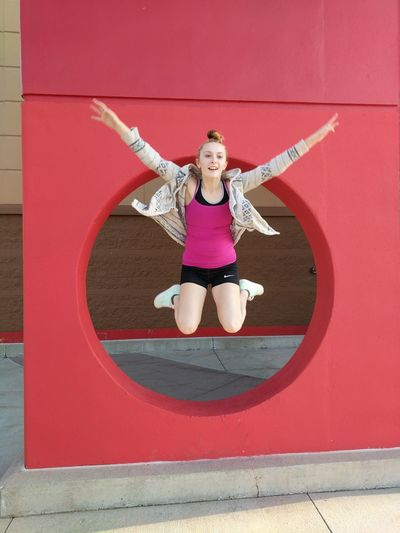 Young woman jumping by red wall with hole on footpath